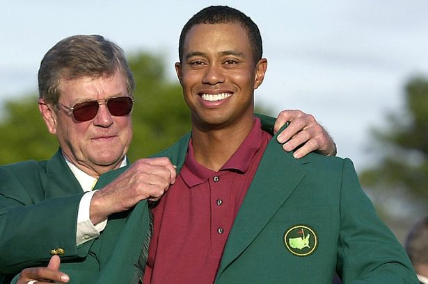 Tiger Woods R receives the green jacket from tournament chairman Hootie Johnson L 14 April 2002 after winning his second straight Masters Tournament at the Augusta National Golf Club
